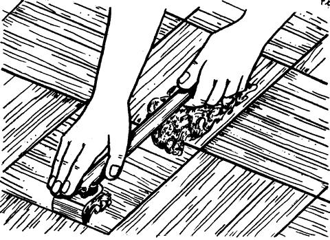 Рис. 25. Циклевка пола циклей с удлиненной ручкой