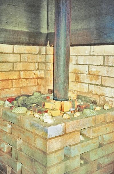 Фото 3.4.12. Металлическая печь обложена кирпичным экраном, а в каменке использовано сочетание фарфора (высоковольтные изоляторы) и булыжников