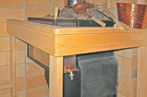 Фото 3.7.21. Деревянное ограждение металлической печи не мешает пользоваться водогрейным баком