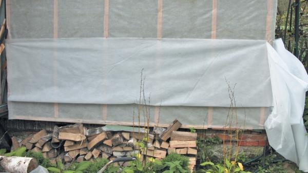 Фото 5.3.3.8. Полная ширина пленки теперь не нужна. Удобно резать ее вдоль прямо на стене, пристрелив несколькими скобами. По шпациям определяется необходимая длина