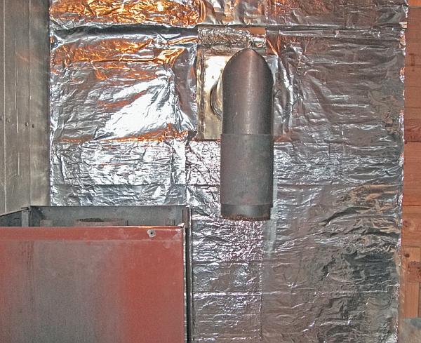 Фото 5.3.7.2. Первым делом был заменен пострадавший в ходе предыдущих ремонтов асбоцементный экран. Новый, как и старый,– двухслойный, с внутренним слоем из толстой алюминиевой фольги, закрепленной на обшивке посредством степлера скобами. Но главное, в месте прохода трубы через стену труба снабжена кожухом, выполненным для упрощения конструкции из вентиляционного патрубка квадратного сечения